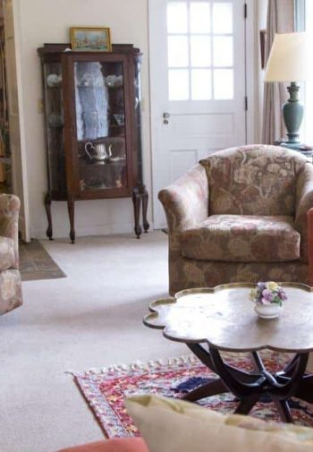 Cozy common room with upholstered sofa and chairs, carpeting, and natural light