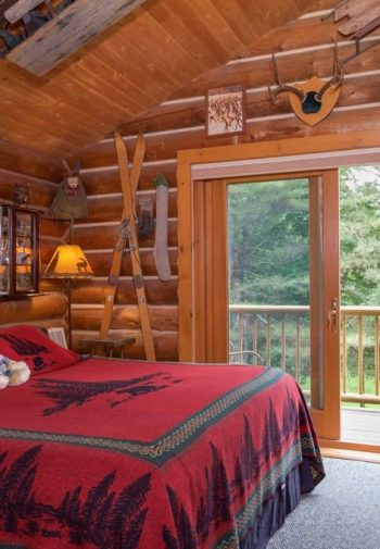 Vaulted guest room with log walls, wood ceiling, two sliding doors, balcony and bed with red woodsy blanket
