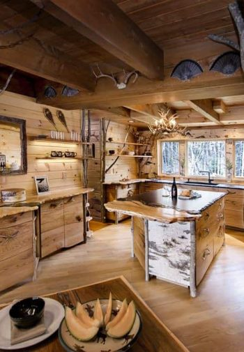 Treehouse kitchen with wood floors, walls and ceiling, triple window over the sink, center island and rustic accents