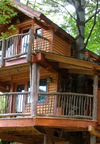 Two-story log tree house with two covered balconies with log railings surrounded by trees
