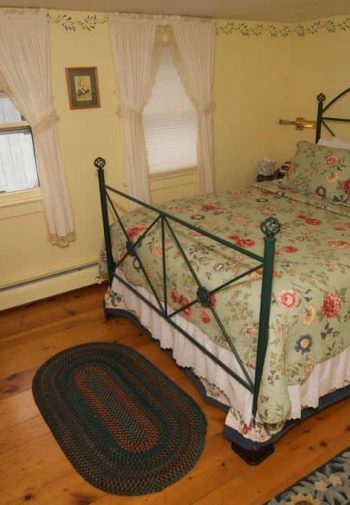 Pale yellow guest room with wood floors, rugs, two windows, green metal bed, and nightstand with lamp
