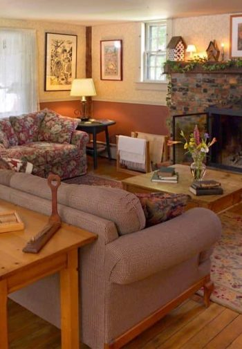 Cozy common area with wood floors, large brick fireplace, upholstered furniture, and several windows