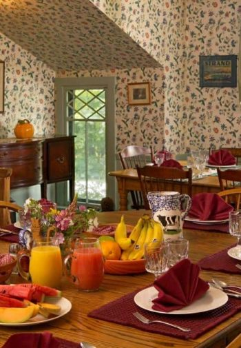 Cozy dining area with paper walls, windows, dining tables and chairs set for breakfast with granola, fruit, juice and flowers