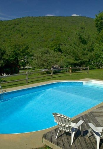 Beautiful crystal clear blue oval swimming pool surrounded by lush green grass and tree-covered hills