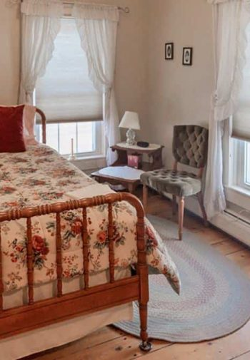 Guest room with wooden twin bed, two windows with white curtains, wide plank floors, rug and two chairs