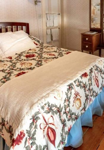 Guest room, wood headboard with quilt-covered bed and ruffled bedskirt, wide plank floors, and vanity dresser with mirror