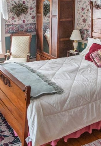 Guest room with floral papered walls, wide plank floors, wood bed with white comforter, nightstands and rocking chair