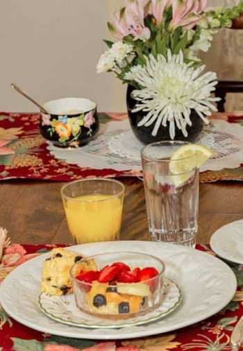Dining table set for breakfast with fresh flowers, fresh fruit and baked scones, orange juice, lemon water and coffee cups