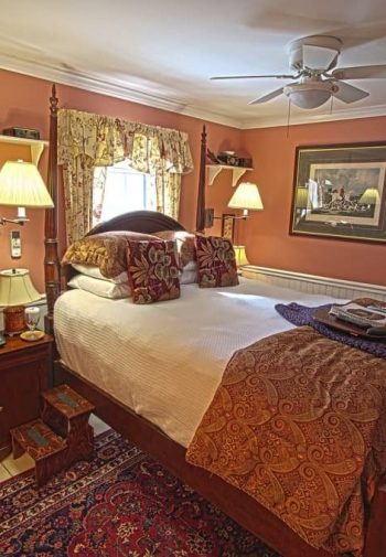 Terracotta guest room with window, four poster bed, nightstands with lamps and writing desk with chair
