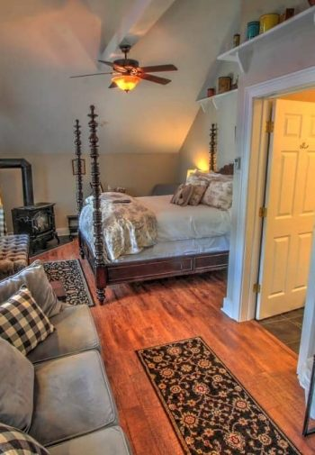 Guest room with slanted ceiling, ceiling fan, four poster bed, window, wood floors, and upholstered sofa