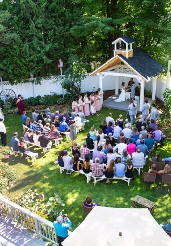 Rows of people witnessing a romantic outdoor wedding under a covered pergola surrounded by grassy lawn and green trees