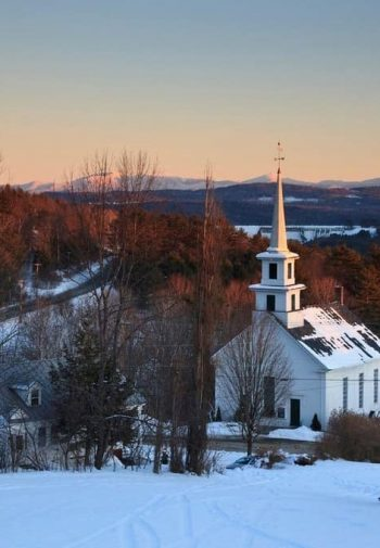 View of old white church surrounded by trees and snow at dusk