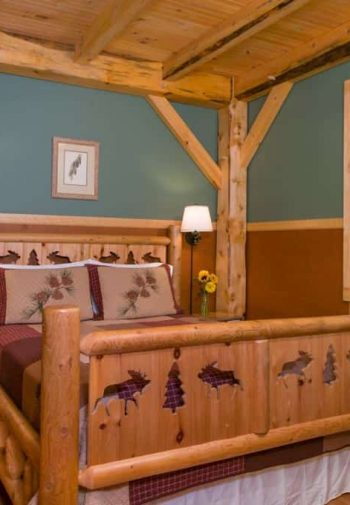 Rustic guest room with carved wooden bed, nightstands with lamps, window, wood floors and exposed beam ceiling