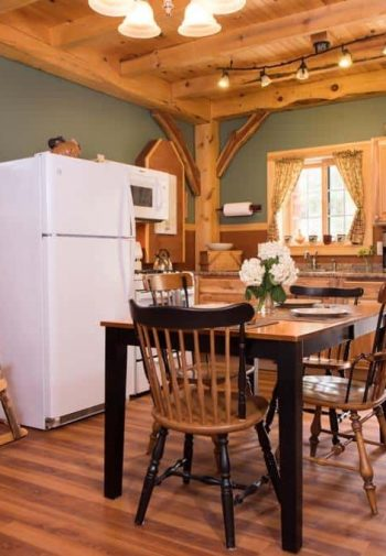 Guest cottage kitchen with wood floors, exposed beam ceiling, kitchen sink window, exterior door, dining table for four, rocking chair