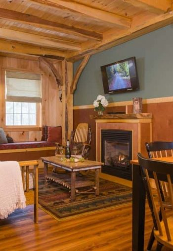 Guest common room with wood floors, exposed beams, fireplace, TV, sofa, rocking chair, and dining table for four