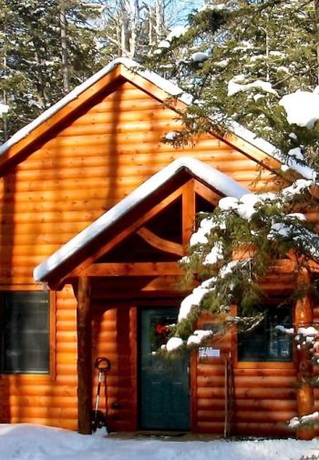 Log cabin with two gables, covered entry, green door, surrounded snow and pine trees