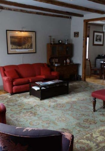 Common sitting room with wood floors, large rug, exposed beams and upholstered furniture