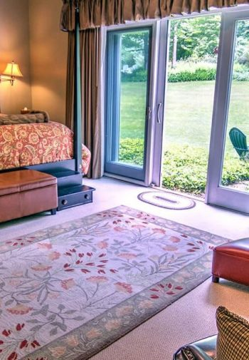 Spacious guest room with triple-panel sliding doors, four poster bed, carpeting and leather chairs