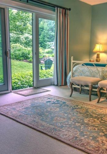 Pretty guest room with light blue walls, triple-panel sliding door, carpeting, king bed, upholstered chairs and carpeting
