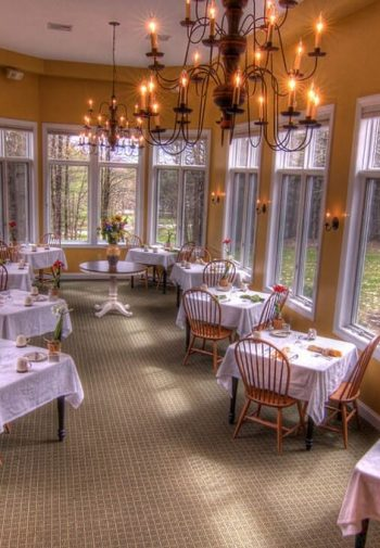 Long spacious dining room surrounded by windows with tall ceilings, chandeliers, and dining tables and chairs and white tablecloths
