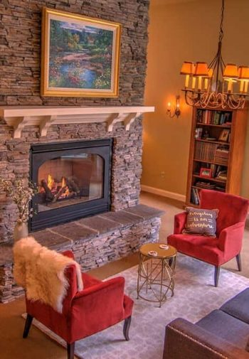 Large stone see-thru fireplace in the middle of the common room with upholstered furniture seating on both sides