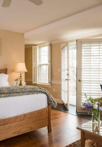 Spacious guest room, beige walls, natural light, wood floors, large bed, sofa and table topped with flowers and wine