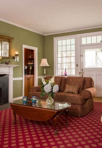 Charming common room with green papered walls, natural light, cozy fireplace with wraparound white mantel, and upholstered furniture