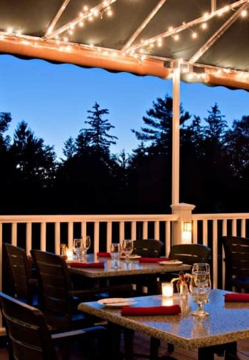 Outdoor covered patio with railing, twinkle lights and several tables and chairs set for a meal with lit candles