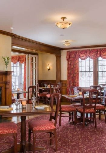 Common dining room with cozy fireplace and wraparound wood mantel, wood floors, dining tables and chairs and large triple window