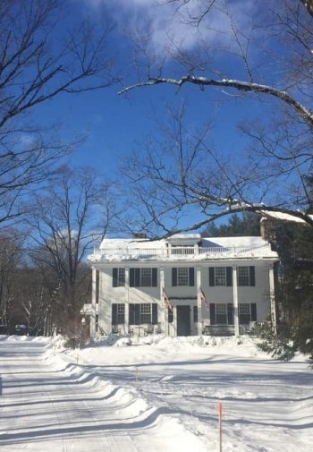 Exterior view of snowy lane leading to two-story white-sided inn amidst bare snow-covered trees and blue skies