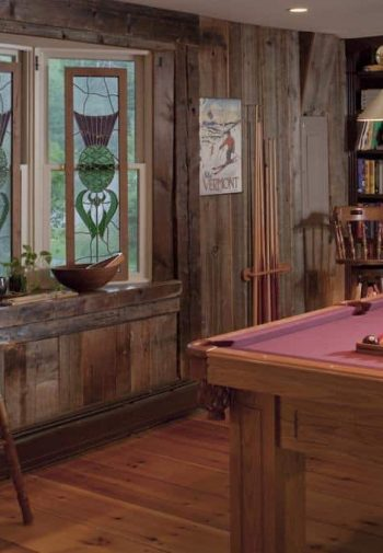 Guest common room with pine floors, pool table, book-filled shelves, bay window and two barstools flanking bar table