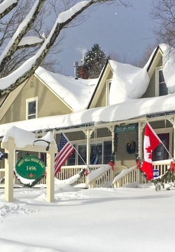 Front exterior of West Hill House B&B in the winter surrounded by fresh white snow and snow-topped trees and roof