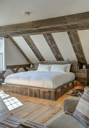 Naturally lit spacious guest room with wide plank wood floors, bed on wood platform with nightlights, rocking chair and sofa