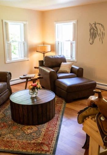 Common room with warm beige walls, wood floors, leather sofa, chair and ottoman, several windows and a TV