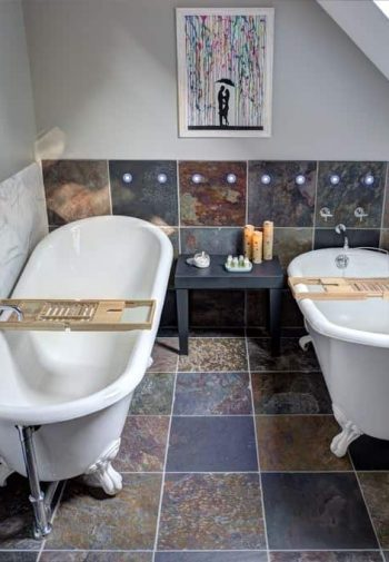 Guest bath, slanted ceiling with window, tile floors and two clawfoot white porcelain tubs