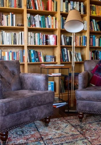 Common room with wide plank wood floors, two walls of book-filled chairs and two cozy leather chairs