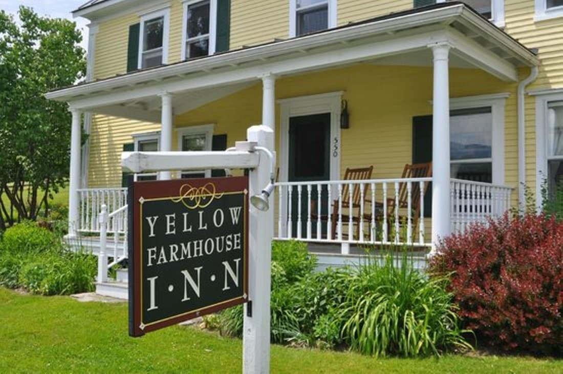 front of yellow house with signage